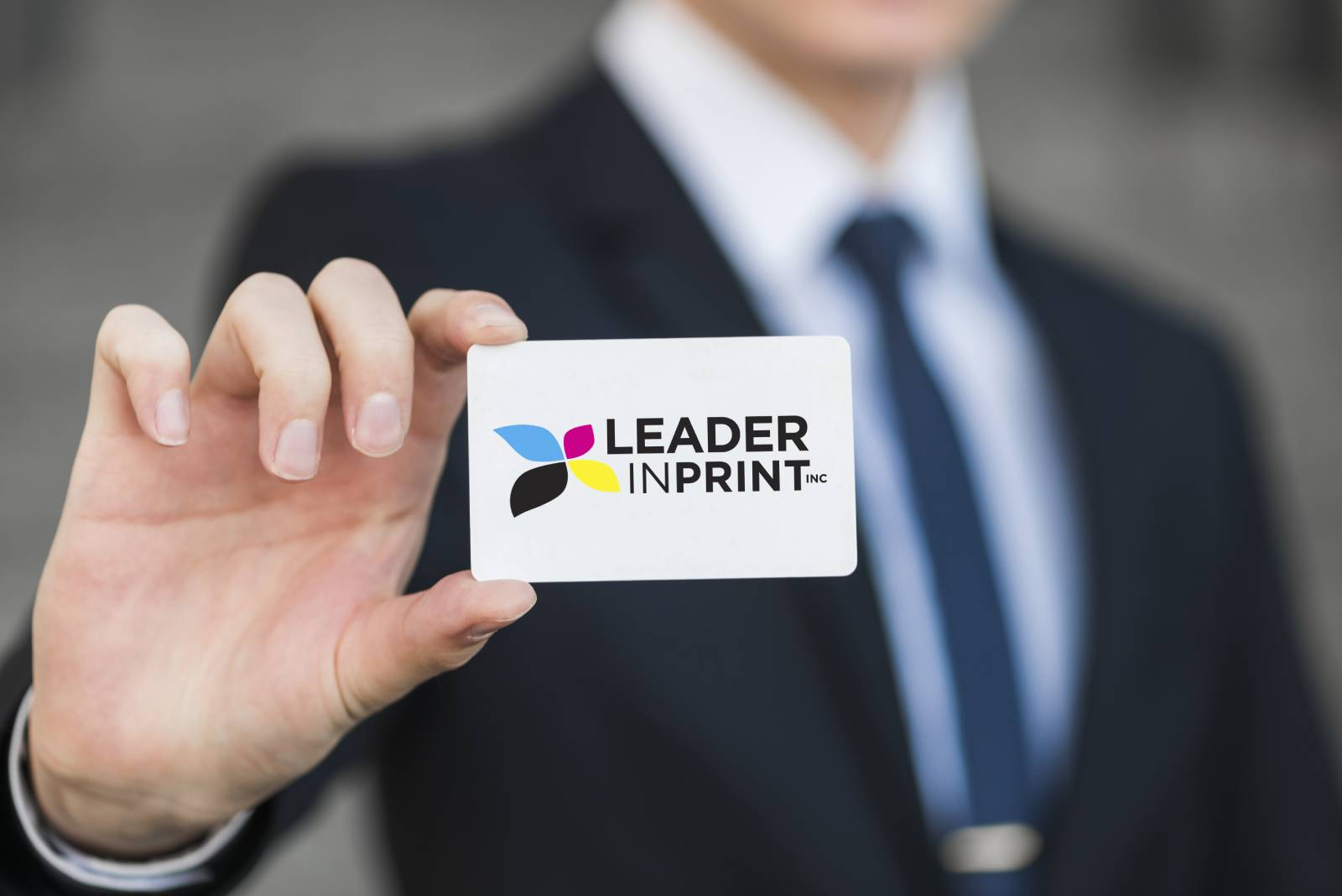 man in a suit holding a leader in print business card